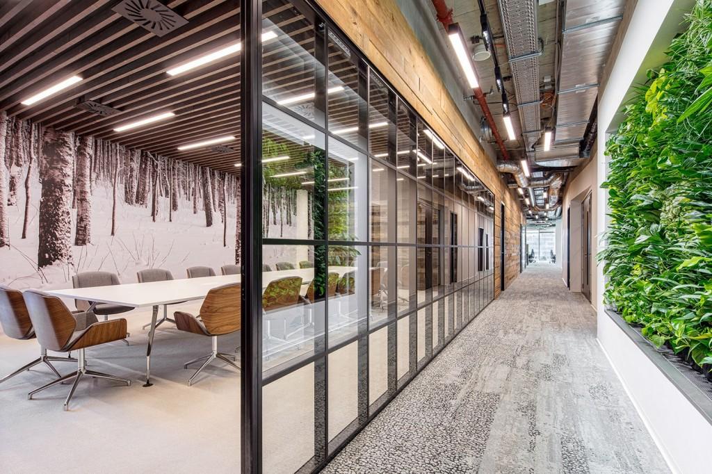 Novo escritório da CA Technologies em Praga possui uma grande sala de reuniões, fechada por divisórias de vidro, que permitem a integração visual do espaço interno com o externo, explorando recursos que remetem à natureza. Crédito: Divulgação Officelovin