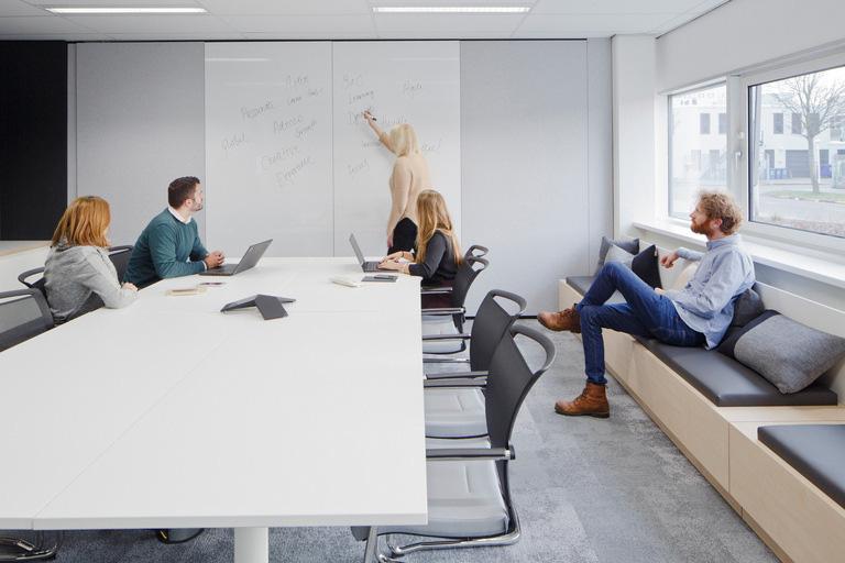A sala de reuniões do escritório da Adecco em Amsterdam, além da mesa tradicional, apresenta assentos laterais com almofadas para favorecer a descontração. Crédito: Divulgação Officesnapshot