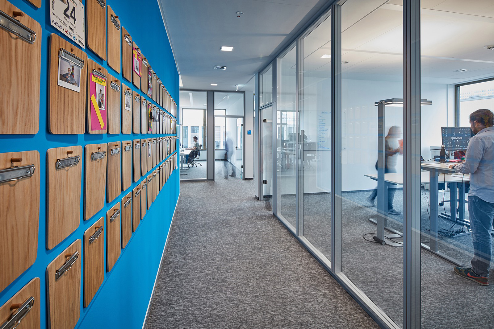 Painel com pranchetas para interação dos profissionais no escritório da LeanIX, Bonn, Alemanha. Crédito reprodução: officelovin