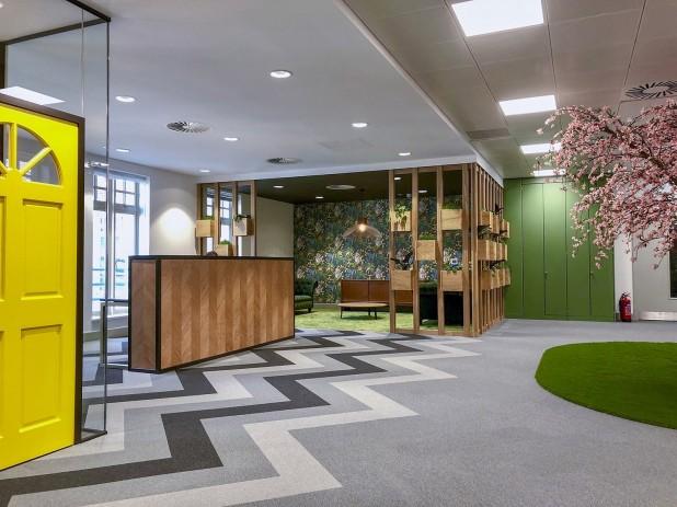 O escritório da New Homes Law na Inglaterra, agrega diversos itens como espaço multicolorido, grama sintética, plantas e muita madeira. Crédito: Reprodução Office Lovin