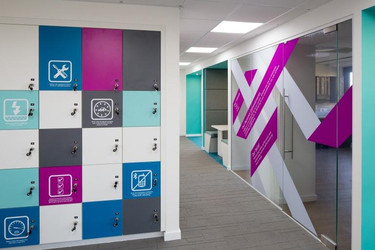 Escritório da Alstom em Bristom, Inglaterra, utiliza uma parede num corredor para colocar os lockers, utilizando adesivos para transmitir algumas mensagens aos colaboradores.