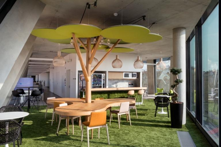 """Na Microsoft House em Milão, Itália, o conceito de biofilia foi empregado com elementos que remetem à natureza de forma figurativa e também bem criativa. Além disso, a copa da """"árvore"""" é composta de materiais acústicos, que auxiliam no conforto ambiental."""