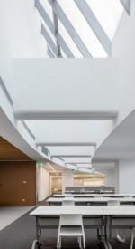 Escritório Sina Plaza, China, com evidente conceito minimalista: móveis neutros, amplos espaços de circulação, pé direito alto, iluminação clara e adequada.