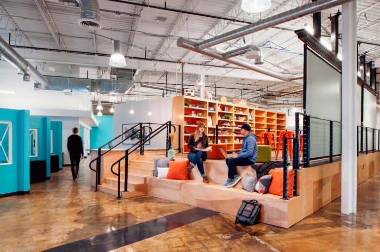 Área da Barber Martin Agency, Virgínia, E.U.A. promove o encontro das pessoas estimulando um convívio cultural. Imagine sendo uma área de exposição em um shopping, com espaço para biblioteca e bate-papo!
