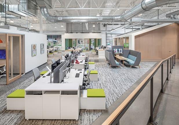 """Ao fundo dessa imagem, podemos ver que o sofá com encosto alto foi utilizado no projeto do escritório norte-americano da Crocs para formatar uma espécie de mini sala de reuniões. Dispostos em """"U"""" com uma mesa ao centro."""